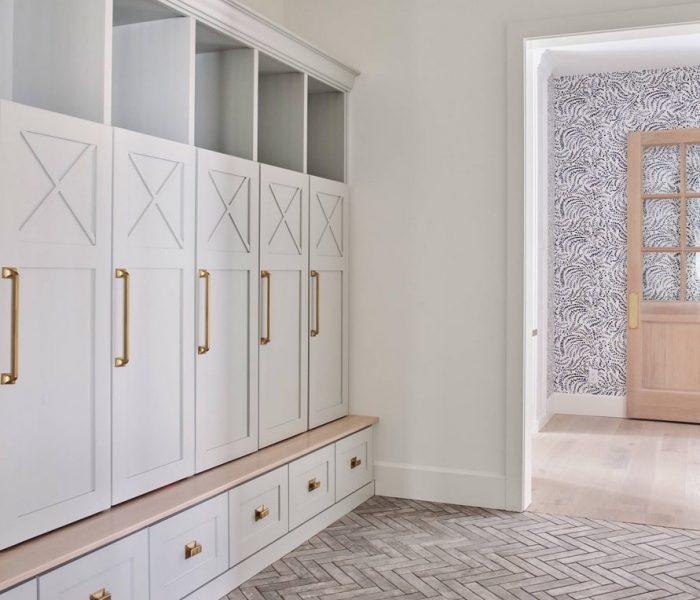 shaker style mudroom cabinetry in white with natural wood and brass accents
