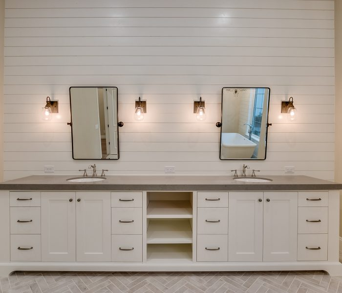shaker style bathroom in white with dark countertops and white shiplap