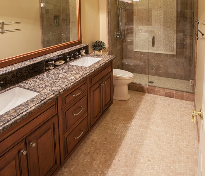 traditional style bathroom vanity in dark wood stain and natural stone quartz