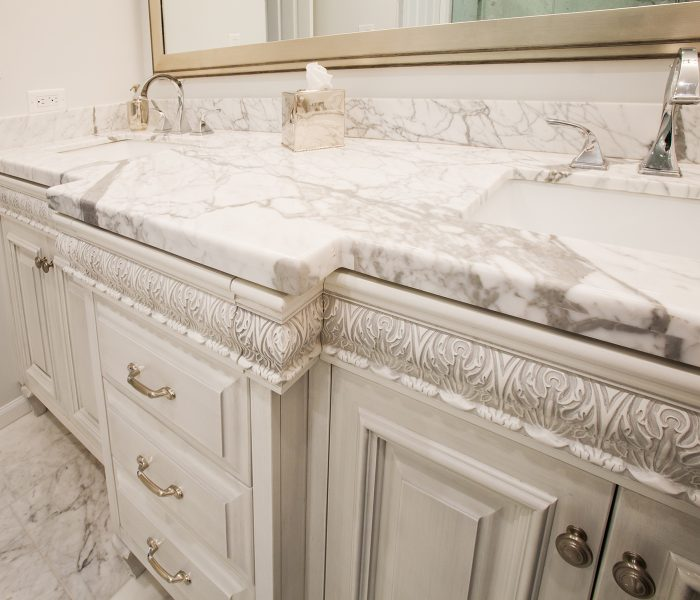 traditional style bathroom vanity in white with white quartz countertops and carved wood trim