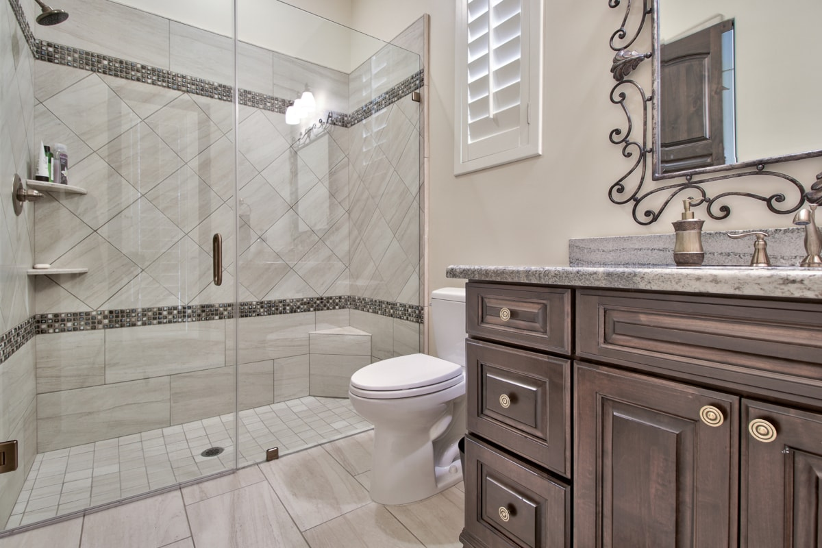 transitional style bathroom vanity in antique wood stain with marbled quartz countertops