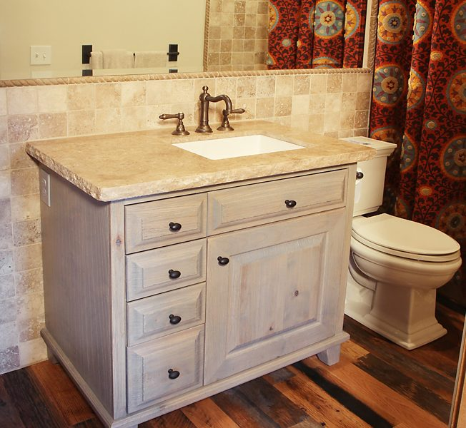 transitional style bathroom vanity in antiqued wood stain with natural stone quartz tabletop