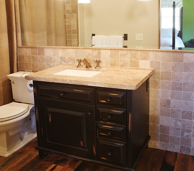 transitional bathroom vanity in dark wood stain with natural stone countertops