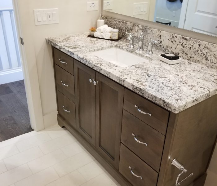 transitional style bathroom vanity in dark wood stain with white quartz countertops