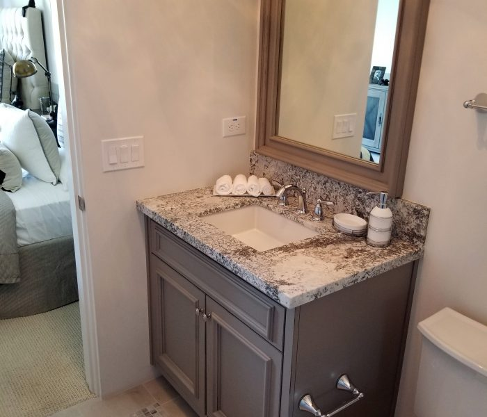 transitional style bathroom vanity in gray with speckled stone quartz countertops