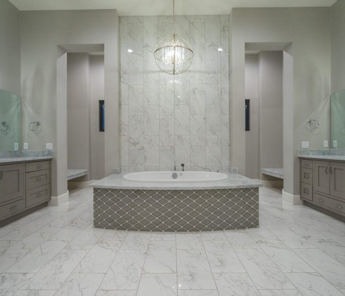 transitional style bathroom vanities in gray with marbled quartz countertops and tile