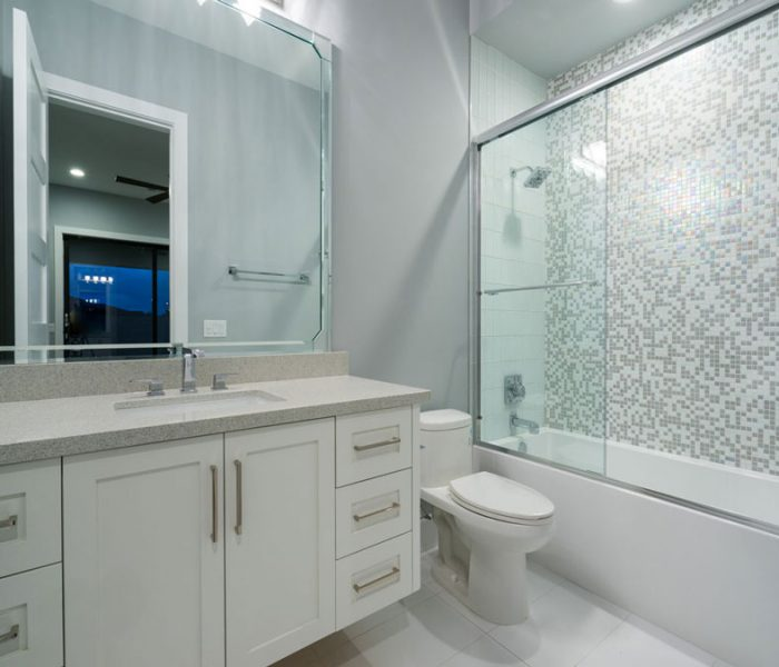 transitional style bethroom vanity in white with gray quartz countertop and metallic spacksplash