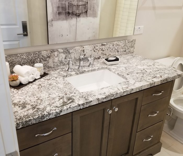 transitional style bathroom vanity in dark wood stain with speckled white quartz