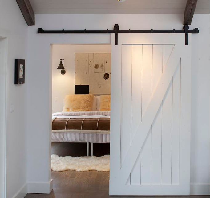 transitional style bedroom in white with barn door entryway