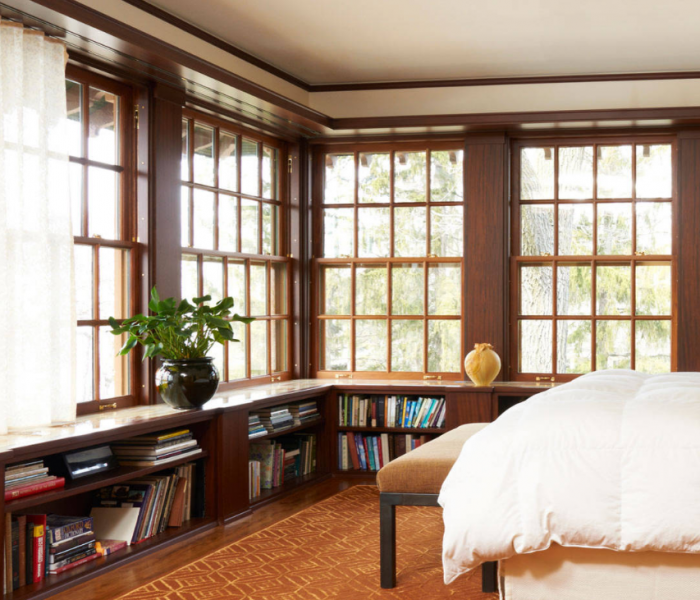 transitional style bookcase below window in dark wood stain