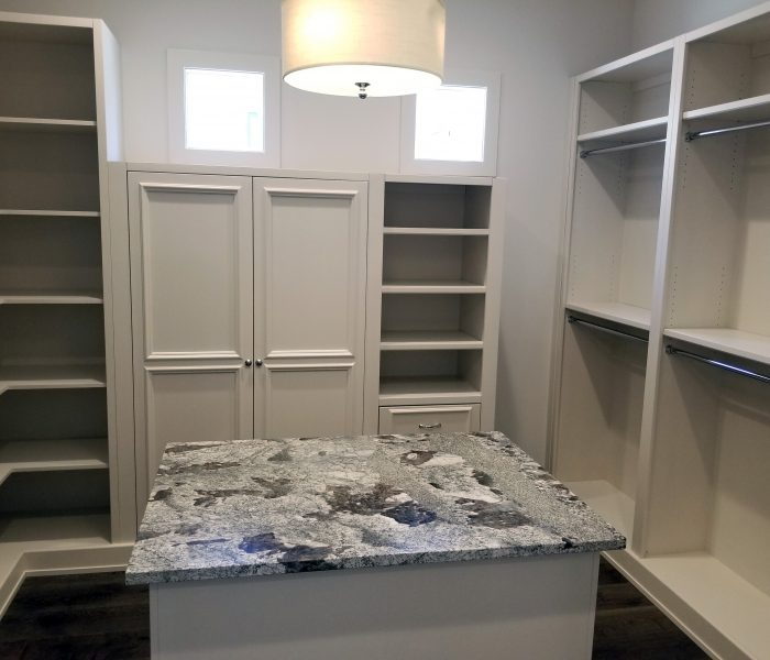 transitional style closet in white with closet island