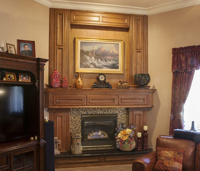 traditional style fireplace in natural wood stain with tan mosaic backsplash tile