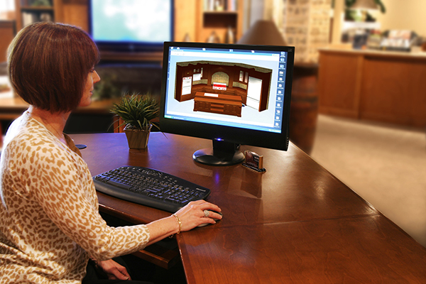 woman designing a kitchen using drafting software on a computer
