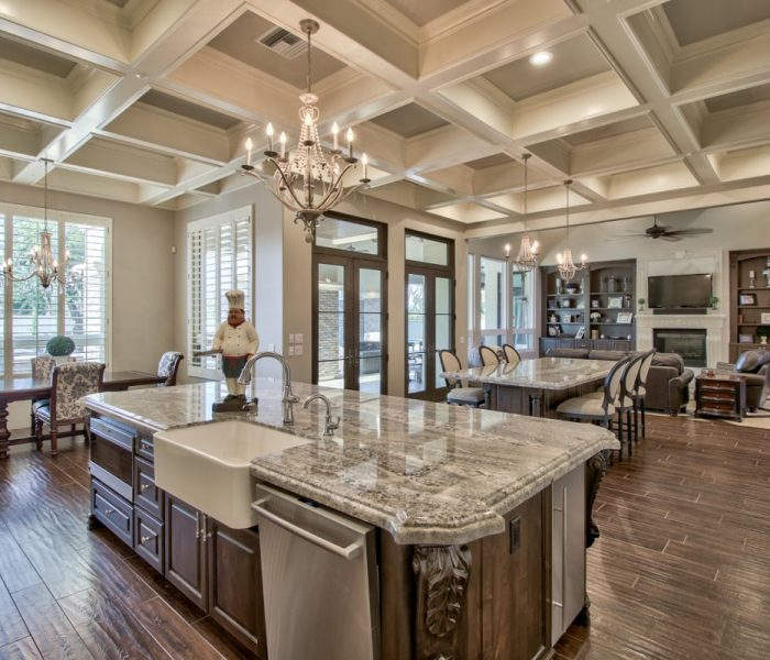 traditional style kitchen in antique wood stain with natural stone quartz countertops and dining table