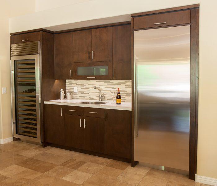 modern style kitchen in dark wood stain with white quartz countertops and modern backsplash