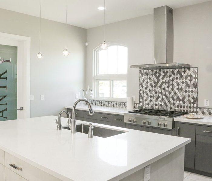 modern style kitchen in two tone gray with white quartz countertops