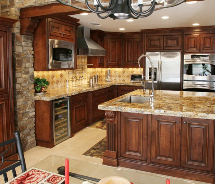 traditional style kitchen in dark wood stain with natural stone quartz countertops