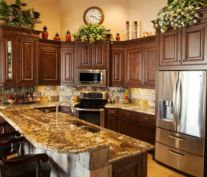 traditional style kitchen in dark wood stain with natural stone quartz countertops and brick