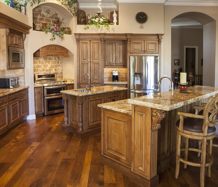 traditional style kitchen in natural wood stain with stone quartz countertops and brick accents