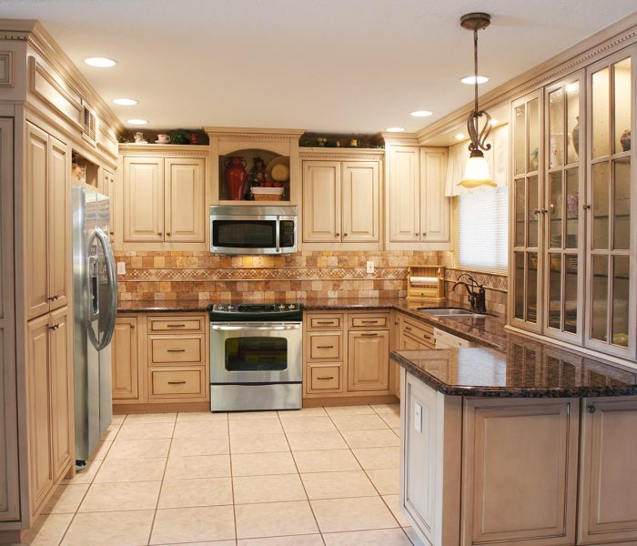 transitional style kitchen in in antique wood stain with black quartz countertops