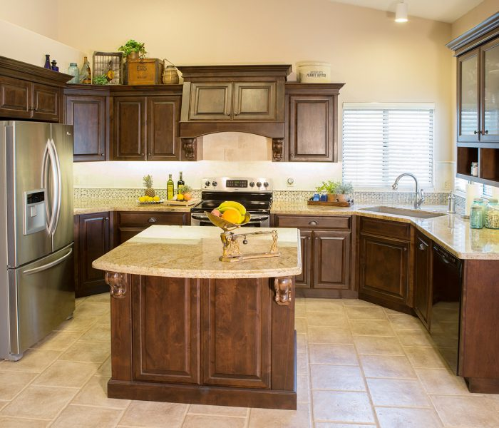 transitional style kitchen in dark wood stain with natural stone quartz countertops and tile accents