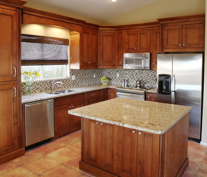 transitional style kitchen in dark wood stain with natural quartz stone countertops