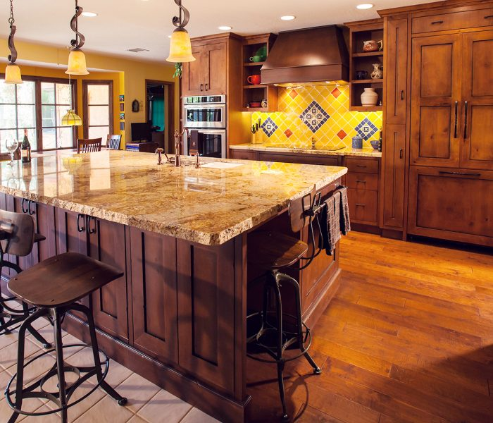 transitional style kitchen in dark wood stain with stone quartz countertops and yellow blue and red backsplash tile