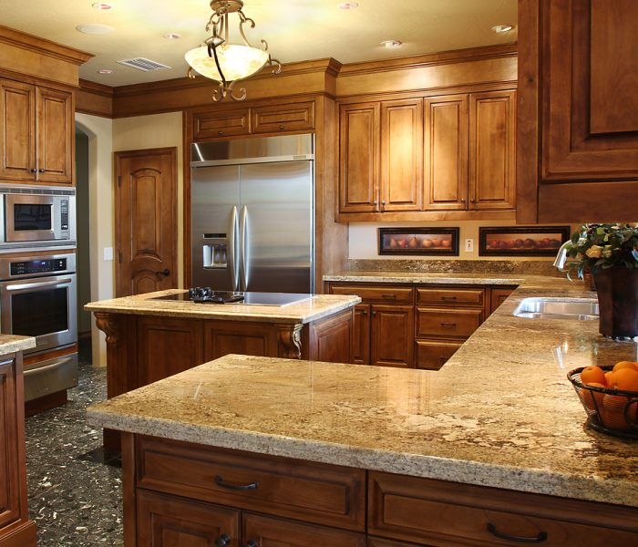transitional style kitchen in dark wood stain with natural stone quartz countertops