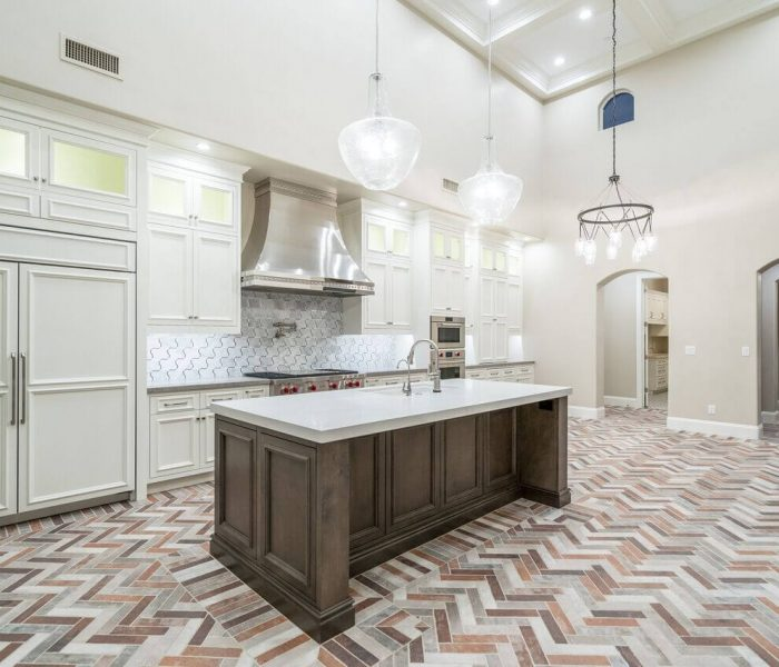 transitional style kitchen in two tone dark wood stain and white with white quartz countertops