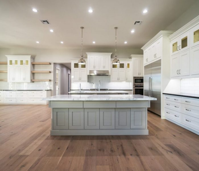 transitional style kitchen in white and natural wood stain with two tone black and white quartz countertops