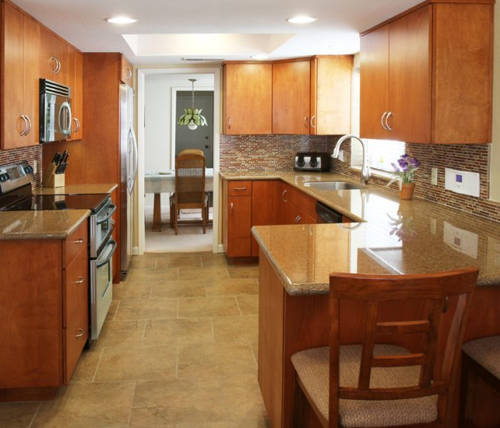 transitional style kitchen in wood stain with quartz countertops and mosaic backsplash tile