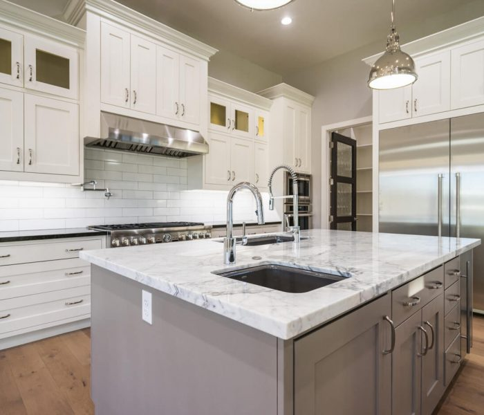 transitional style kitchen in gray with white quartz countertops