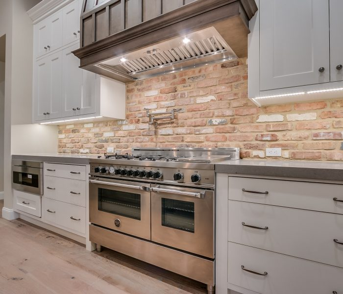 transitional style kitchen in white and gray with stainless stove