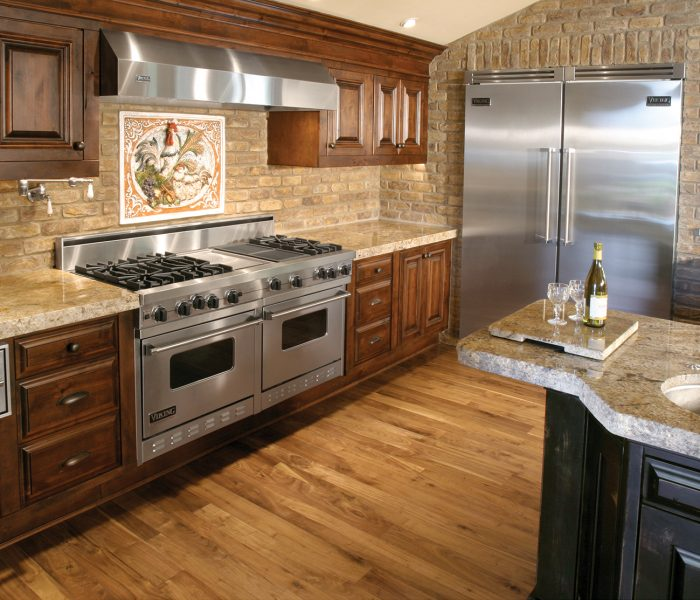 transitional style kitchen in two tone black and dark wood stain with natural stone quartz countertops