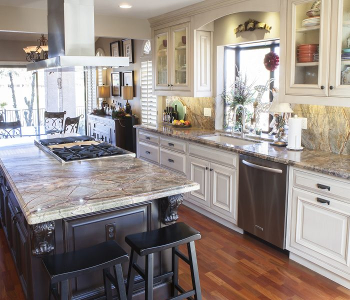 transitional style kitchen in two tone black and white paint with natural stone quartz countertops