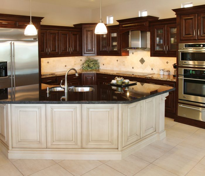 transitional style kitchen in two tone antique white and dark wood stains with black quartz countertops