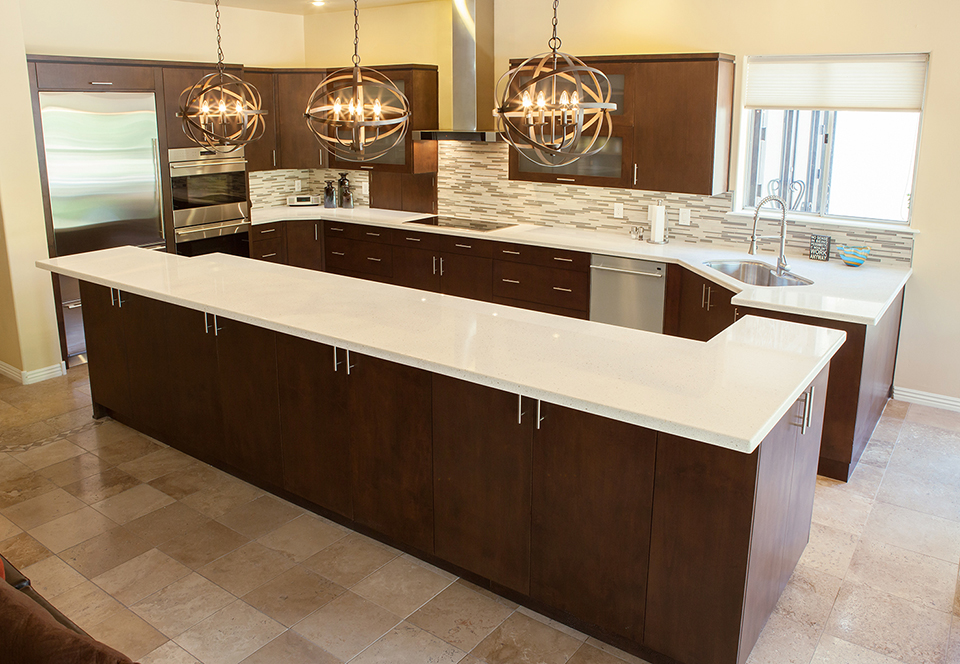 transitional style kitchen in dark brown wood stain with white quartz countertops