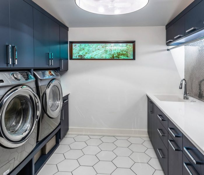 modern laundry room cabinetry in blue with white quartz counter tops