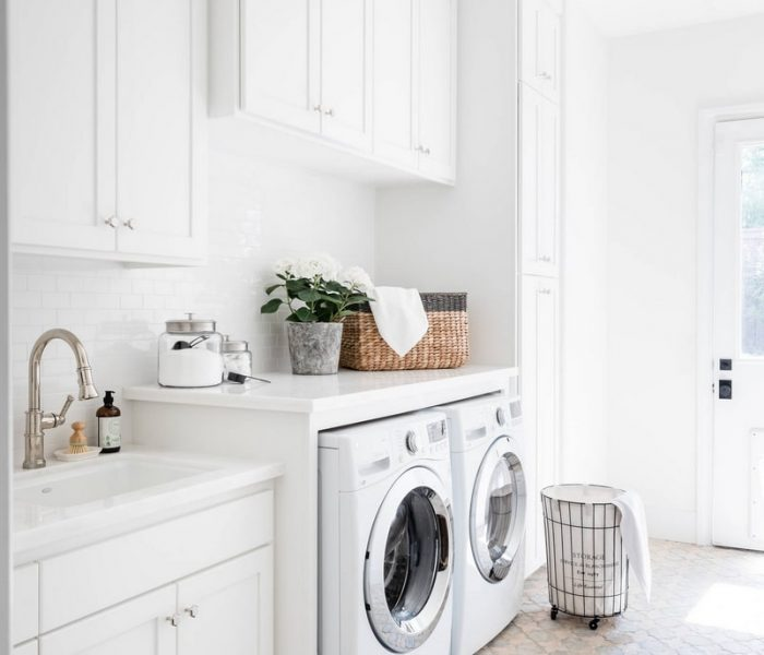 modern laundry room in white with white quartz countertops