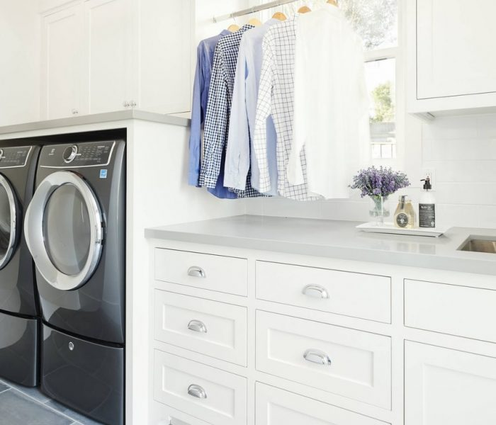 modern laundry room cabinetry in white with gray counter tops
