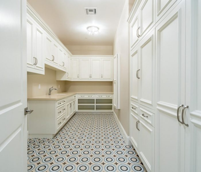 traditional style laundry room in white and tan