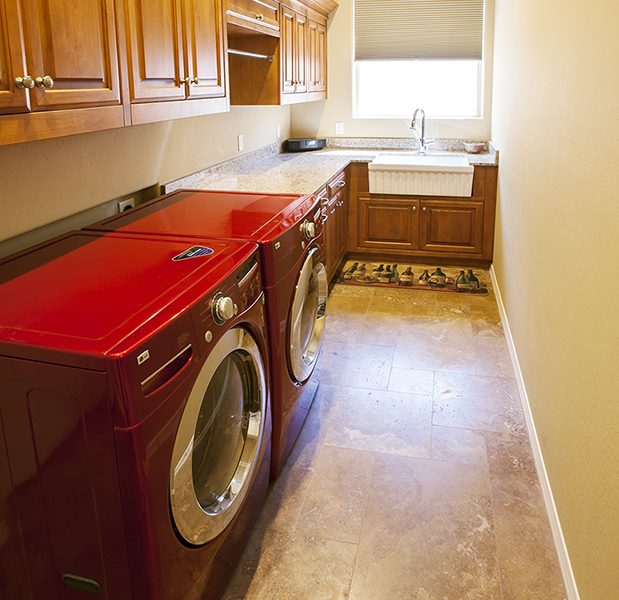 traditional style laundry room in natural wood stain and white quartz countertops