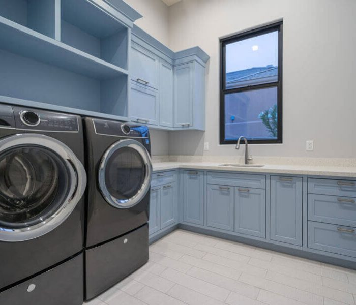 transitional style laundry room in blue with white quartz countertops