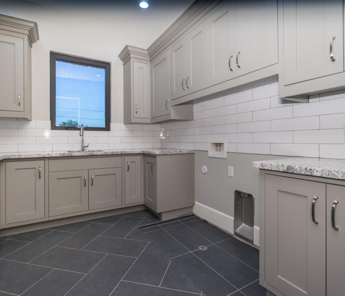 transitional laundry room in gray with white tile backsplash