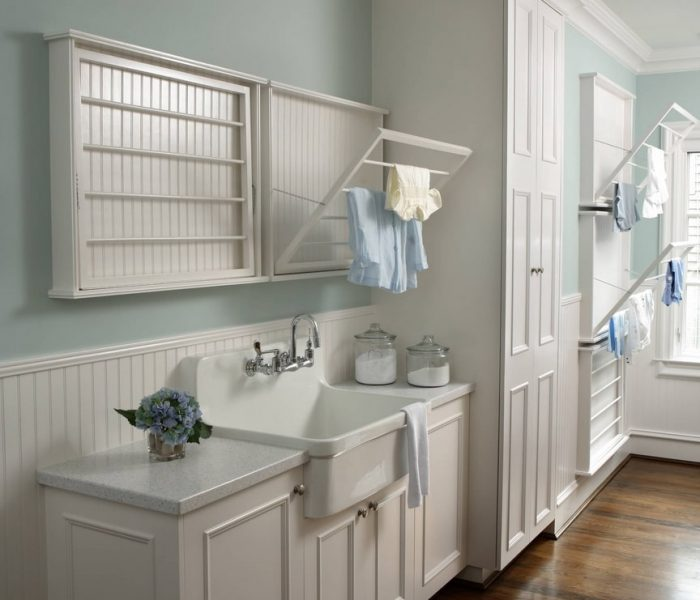 traditional laundry room cabinetry in white with teal accents