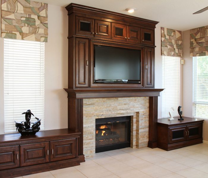 transitional style media wall fireplace in dark wood stain and stone brick