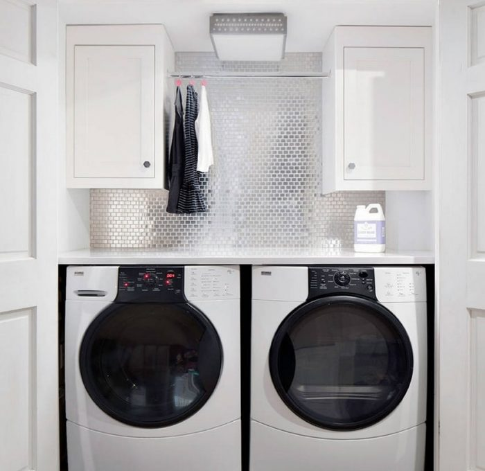 modern laundry room in white with reflective backsplash