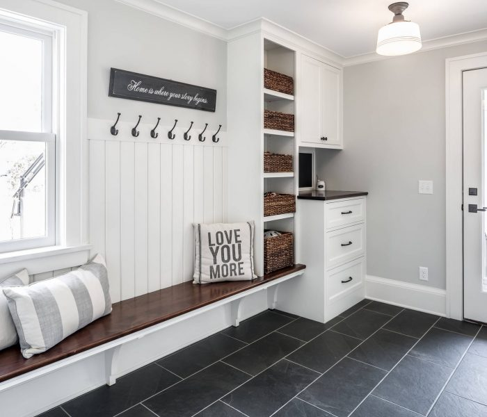 shaker style mudroom cabinetry in white with natural wood bench