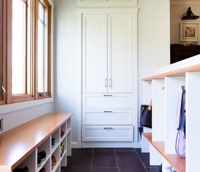 shaker style mudroom hallway cabinetry in white with natural wood benches