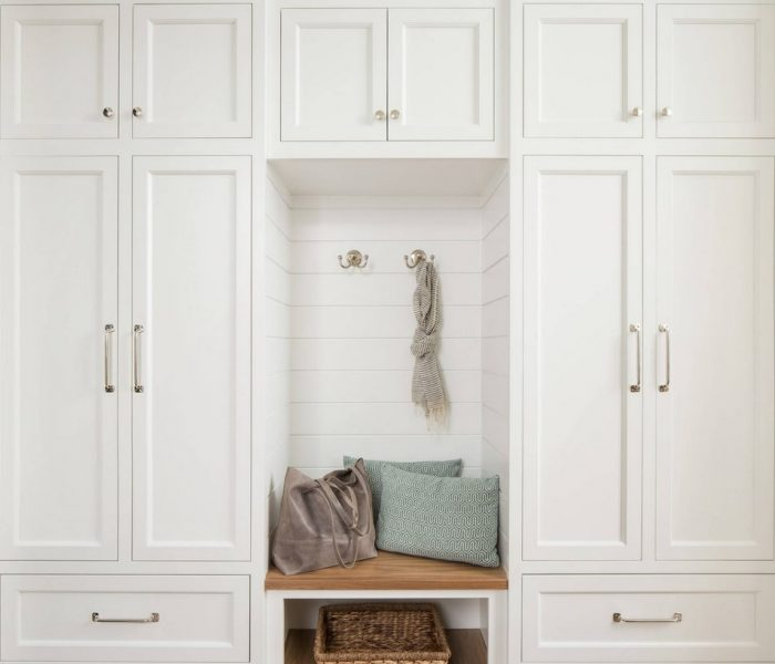 shaker style mudroom cabinetry in white with natural wood bench and brass accents